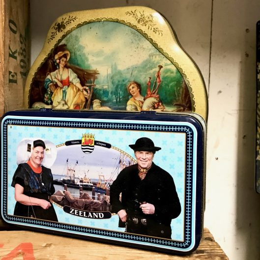 A tin of wrapped candy. With two people in traditional Dutch costume, and some fishermen boats in the background.