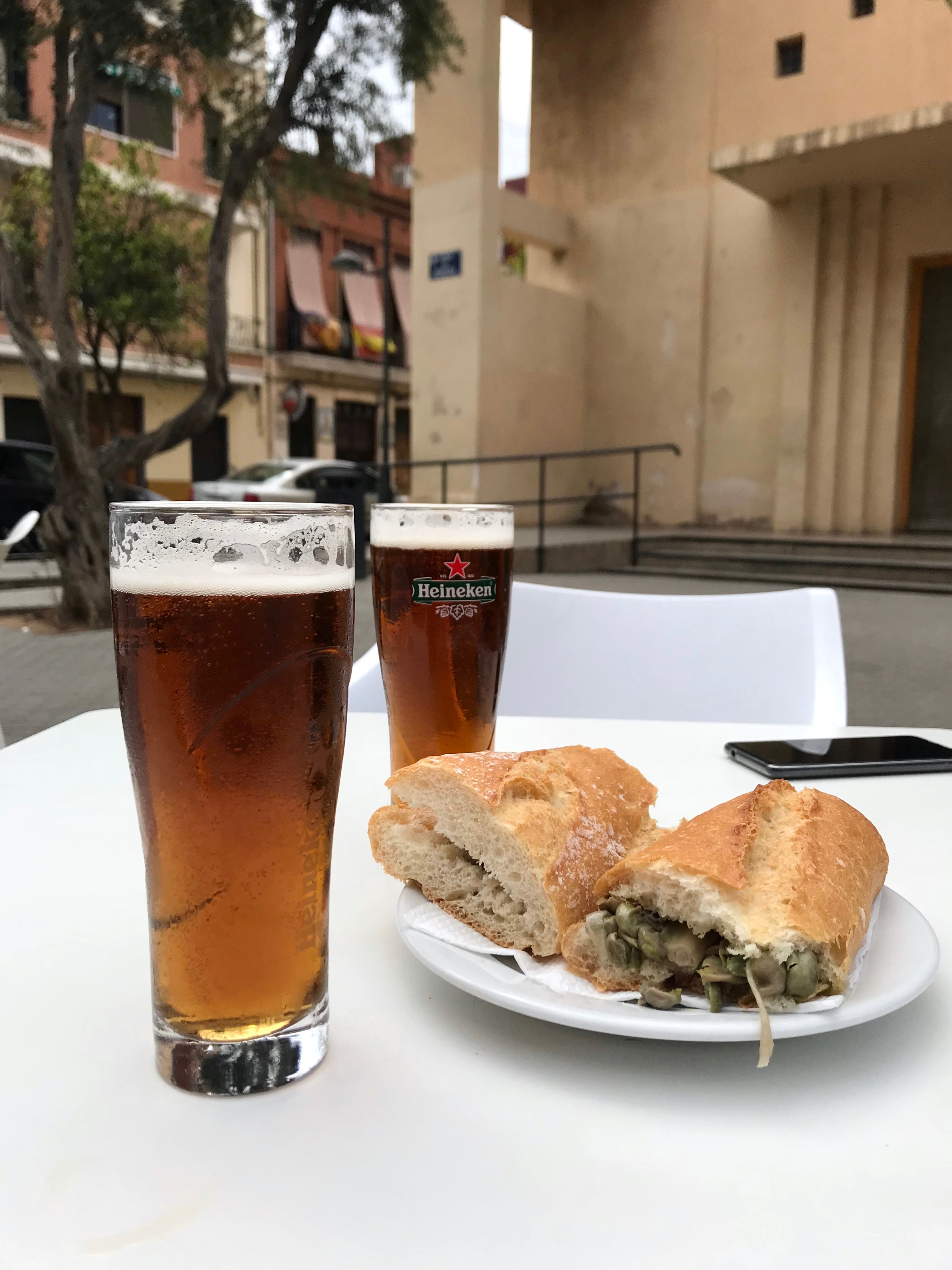 Two beers and a bocadillo sandwich with favs beens