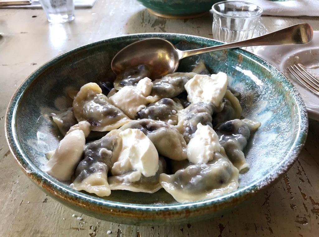 Pierogi dumplings with bilberries and cream