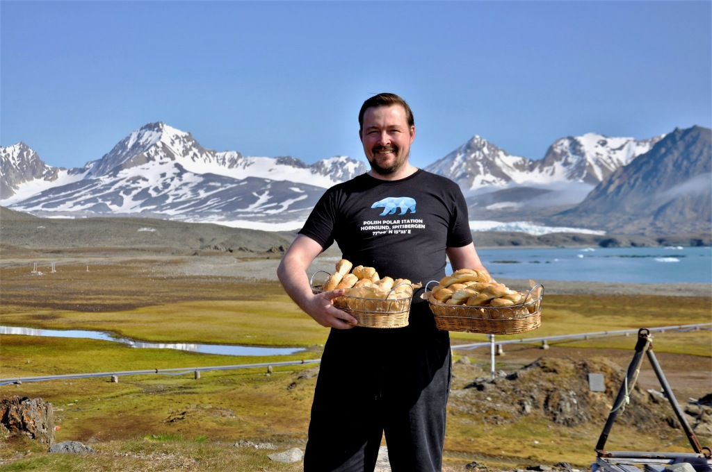 Man holding baskets with breads with mountains in the background