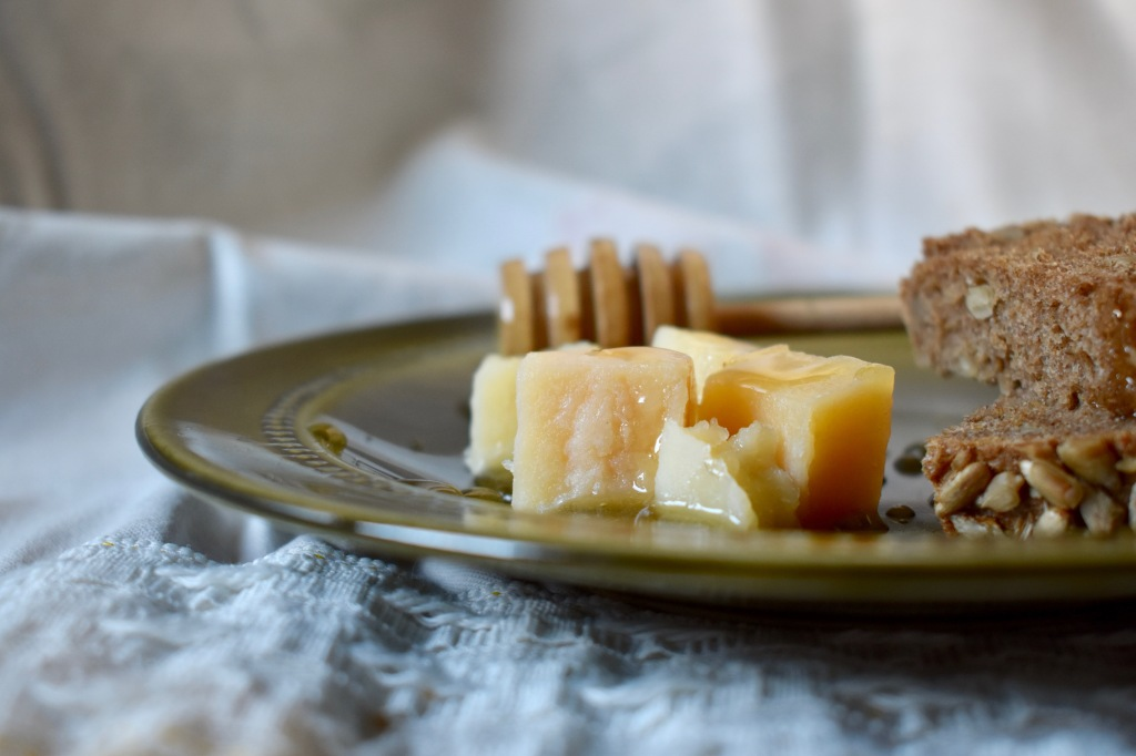 Pieces of cheese with honey and bread