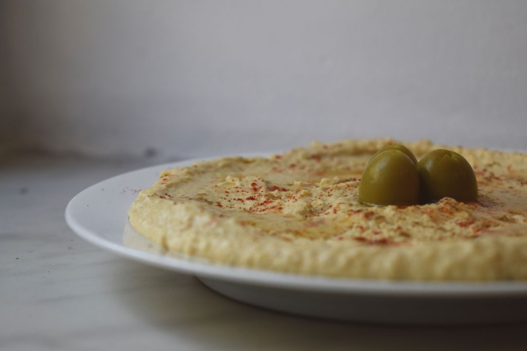 Hummus with olives and paprika on a white plate