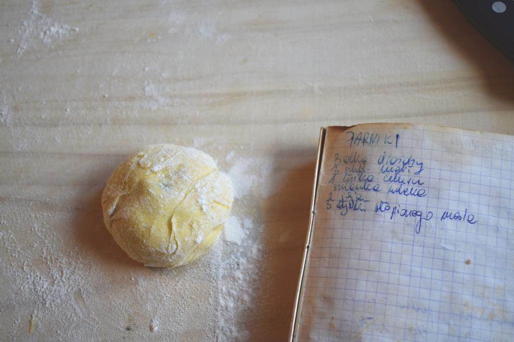 A bun and an open notebook with handwritten recipe in Polish on a floured pastry board