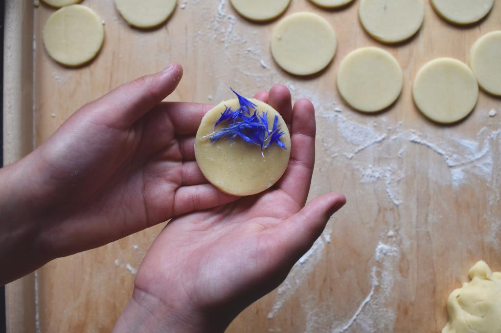 two hands holding ready to bake shortbread biscuit with fresh blue cornflower petals