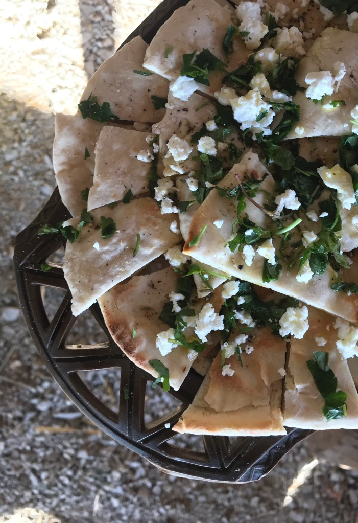 pieces of flatbread on a tray with crumbled cheese and chopped herbs