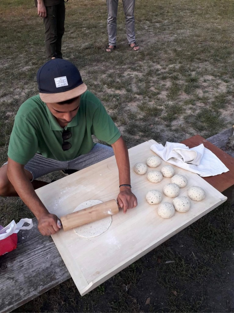 man rolling out pastry for flatbreads outdoors