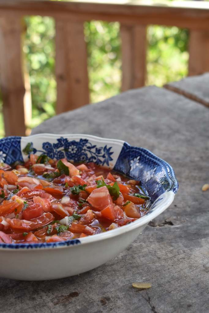 chopped tomato and herb salad in a blue and white bowl