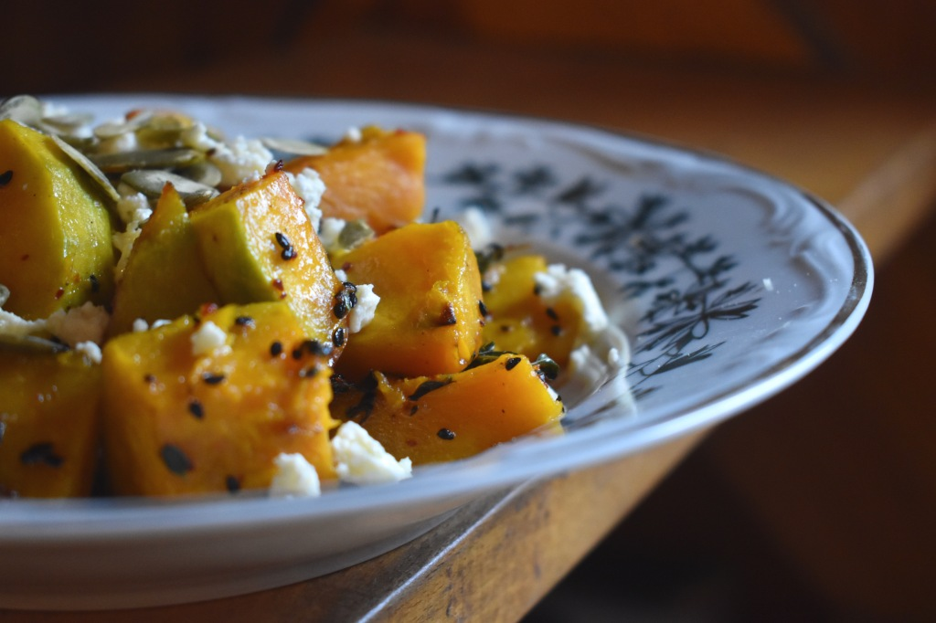 a plate of pumpkin pieces with cheese, nigella seeds and pumpkin seeds