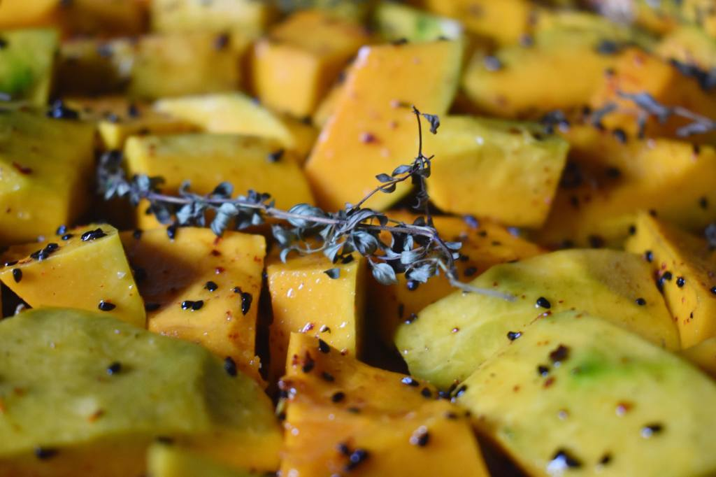 pieces of pumpkin covered with black seeds and a branch of dried herbs