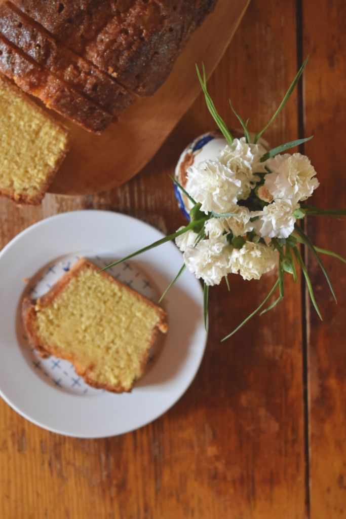 slice of loaf cake on a white plate with white flowers
